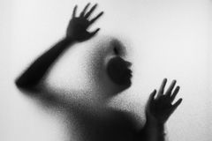 Horror woman behind the matte glass in black and white. Blurry h. And and body figure abstraction.Halloween background.Black and white picture Stock Photography