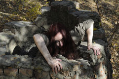 Horror woman from well. Horror woman crawling from a brick well Stock Photos