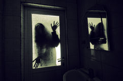 Horror woman in window wood hand hold cage scary scene halloween concept Blurred silhouette of witch Stock Image