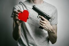 Horror y tema de las armas de fuego: suicidio con un arma en su mano y un corazón rojo en un fondo gris en el estudio fotografía de archivo libre de regalías