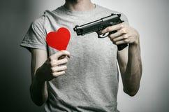 Horror y tema de las armas de fuego: suicidio con un arma en su mano y un corazón rojo en un fondo gris en el estudio Fotografía de archivo