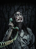 Horror zombie girl calling by phone. Portrait of the horror zombie girl calling by telephone. Scary Royalty Free Stock Photography