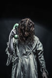Horror zombie girl calling by phone Royalty Free Stock Image