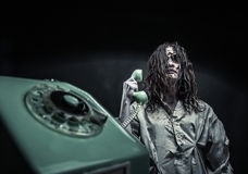 Horror zombie girl calling by phone Stock Photos