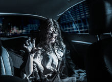 Horror zombie woman with bloody face in the car Stock Photos