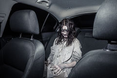 Horror zombie woman with bloody face in the car Stock Photo