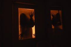 Horrorfrau in Griffkäfigs des Fensters Szenen-Halloween-Konzept des hölzernen Handfurchtsamem verwischte Schattenbild der Hexe Stockbilder