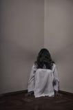 Horrorful dziewczyny obsiadanie przy kątem fotografia royalty free