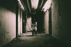 Horrorszene einer furchtsamen Frau in der dunklen Halle stockfotografie
