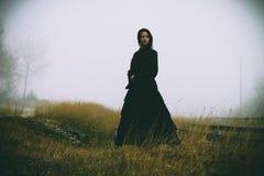 Horrorszene einer furchtsamen Frau im schwarzen Kleid Stockfotos