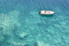 Hors-bord ancré dans l'eau peu profonde de turquoise Photographie stock libre de droits