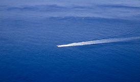 Hors-bord avec la traînée de sillage de lond derrière en mer bleue parfaite Images stock