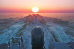 Hors-bord sur la mer au temps de coucher du soleil images stock