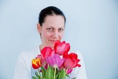 Hors de la jeune fille de foyer avec le bouquet des tulipes rouges sur le fond blanc photo libre de droits