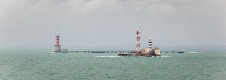Horsburgh Lighthouse and Abu Bakar Maritime Base. Horsburgh Lighthouse on Pedra Branca Island of Singapore and Abu Bakar Maritime Base owned by Malaysia in the Royalty Free Stock Images