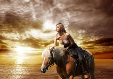 Horse. A beautiful woman riding a horse on the beach Stock Photos