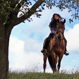 On a horse. East beautiful woman on a horse against the dark blue sky Royalty Free Stock Images