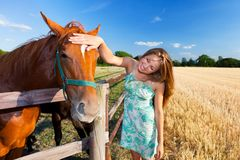 Horse and blond girl in paddock on summers Stock Photo