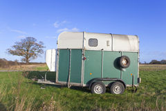 Horse box. A small horse box standing in a grass field under a blue autumn sky Royalty Free Stock Photos