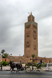 A horse and buggy ride past the tower of Koutoubia Mosque in Marrakesh, Morocco. Stock Photos