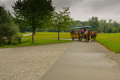Horse-bus. Omnibus,  horses-drawn `bus` is transporting  tourists around the gardens of the mansion on the `Herren insel`, the isle of the men, in Chiemsee Stock Image