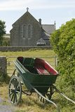 Horse Carriage and Church. A horse-drawn carrage is standing in front of a church on the Aran Islands while the horse is likely grazing elsewhere. This royalty free stock photo