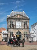 Horse carriage with coachman and his assistant in front of the Waag in Gouda, Netherlands Stock Photos