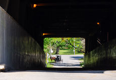 Horse and carriage through covered bridge Royalty Free Stock Images