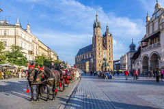 Horse and carriage in front of the St. Mary's Basilica in Kraków. KRAKOW, POLAND - OCT 7, 2014: Horse and carriage in front of the St. Mary's Basilica in Krak stock photo