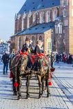 Horse and carriage in front of the St. Mary's Basilica in Kraków. KRAKOW, POLAND - OCT 7, 2014: Horse and carriage in front of the St. Mary's Basilica in Krak royalty free stock image