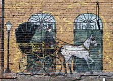 Horse and carriage mural. Mural on a stone wall in Nashville Tennessee depicting white horse drawing a black and gold vintage carriage royalty free stock photography