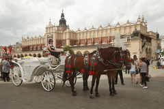 Horse carriage near the Cloth Hall building. Krakow, Poland, Jun. Horse carriage in the square on the building background Cloth Hall. Krakow, Poland, June 17th Stock Image