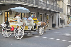 Horse Carriage and tourists in French Quarter of New Orleans, Louisiana Stock Photography