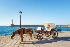 Horse carriage for transporting tourists in old port of Chania on Crete, Greece Royalty Free Stock Photo