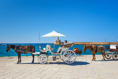 Horse carriage for transporting tourists in old port of Chania on Crete, Greece Royalty Free Stock Images