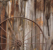Horse Carriage Wheel. A metal horse carriage wheel against a barn wall stock image