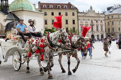 Horse carriages carry tourists for sight-seeing,  Krakow, Poland Stock Photos