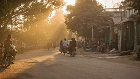 Horse carriages on common Asian dusty road and transport traffic on a street with cars, motorbikes a Royalty Free Stock Photo
