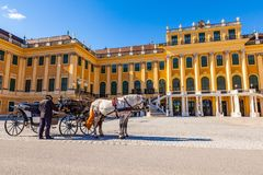 Horse coach and a coachman in front of the Schonbrunn Palace. Vienna, Austria - August 9, 2011 :  Horse coach and a coachman in front of the Schonbrunn Palace in Royalty Free Stock Images