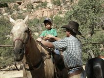 Horse Corral at Zion National Park. A wrangler helps a park guest saddle up for the horseback ride at Zion National Park Royalty Free Stock Image