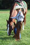 Horse and Cowboy. A little cowboy grazing his brown horse in a pasture with fresh green grass royalty free stock photos