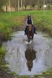 Horse cross country teenage competition jumping tree trunks and jumps over barrels of water and colored bars. The competitions are in europe girl wearing black Stock Photos