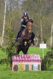 Horse cross country teenage competition jumping tree trunks and jumps over barrels of water and colored bars Stock Images
