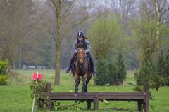 Horse cross country teenage competition jumping tree trunks and jumps over barrels of water and colored bars Stock Photography