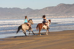 Horse a day at the beach. Two people running horses on beach stock images