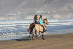 Horse a day at the beach. Two people running horses on beach royalty free stock photos