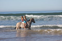 Horse a day at the beach. Two people running horses on beach royalty free stock photography