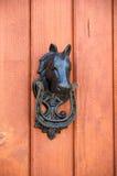 Horse door knocker. Door knocker in the shape of horse and horse-shoe stock photography