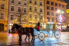 Horse-drawn μεταφορά πριν από το Sukiennice στο κύριο τετράγωνο αγοράς στην Κρακοβία, άποψη νύχτας, POL Στοκ εικόνα με δικαίωμα ελεύθερης χρήσης