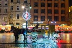 Horse-drawn μεταφορά πριν από το Sukiennice στο κύριο τετράγωνο αγοράς στην Κρακοβία Στοκ Φωτογραφίες